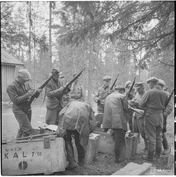 Suomussalmen rajakylien asukkaille jaettiin desanttien varalta aseita heinäkuussa 1943. Kirjan kuvitusta. SA-kuva.